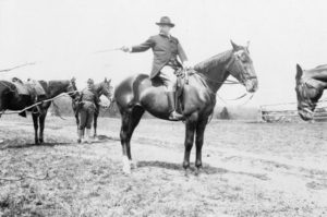 Black and white photo of Theodore Roosevelt on a horse, selecting the next member of the outing party for the next jump over the hurdles, 1907.